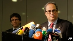 Former Catalan leader Carles Puigdemont, left, and Catalan president Quim Torra, right, attend a news conference in Berlin, Germany, May 15, 2018.