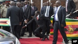 FILE: Zimbabwean President Robert Mugabe, center, falls after addressing supporters, at Harare International Airport upon his return from an African Union summit in Ethiopia, Feb. 4, 2015.