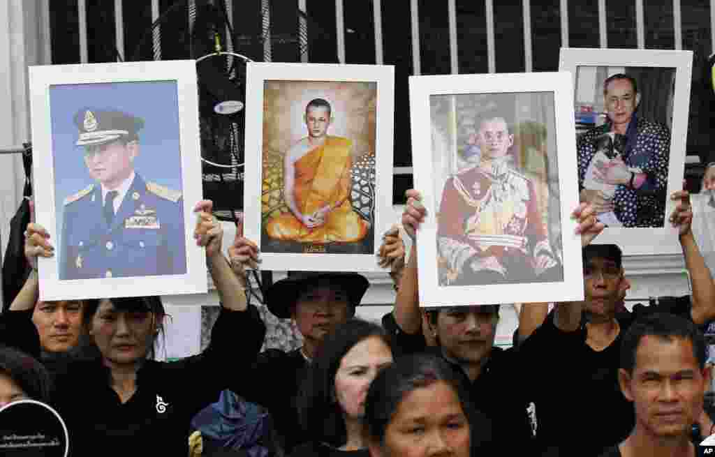 Thai mourners hold up portraits of the late King Bhumibol Adulyadej near Grand Palace to take part in the Royal Cremation ceremony in Bangkok, Thailand, Wednesday, Oct. 25, 2017. Bhumibol's death at age 88 on Oct. 13, 2016 after a reign of seven decades sparked a national outpouring of grief and a year of mourning. (AP Photo/Sakchai Lalit)