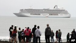Historic Arctic Cruise: This Aug. 21, 2016, photo shows people preparing to take a polar plunge in the Bering Sea in front of the luxury cruise ship Crystal Serenity, which anchored just outside Nome, Alaska. The ship made a port call as it became the largest cruise ship to ever go through the Northwest Passage, en route to New York City.