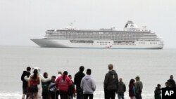 FILE - People prepare to take a polar plunge in the Bering Sea in front of the luxury cruise ship Crystal Serenity, which anchored just outside Nome, Alaska, Aug. 21, 2016. The ship made a port call as it became the largest cruise ship to ever go through the Northwest Passage, en route to New York City.