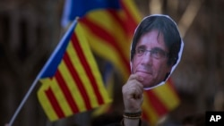 A demonstrator holds a cut-out of Catalonia's ex-president Carles Puigdemont during a protest outside Catalonia's parliament in Barcelona, Spain, Jan. 30, 2018.