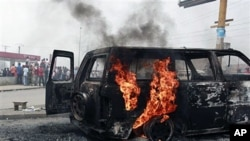 Local residents look on as a UN vehicle, set on fire by militant student supporters of Laurent Gbagbo, burns in the Riviera 2 neighborhood of Abidjan, 13 Jan 2011.