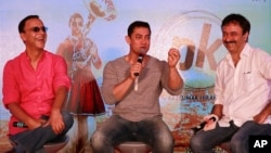 "FILE - Director Rajkumar Hirani, (R), and producer Vidhu Vinod Chopra, (L), enjoy a lighter moment as Bollywood actor Aamir Khan speaks during the unveiling of the second poster of his upcoming film ""PK"" in Mumbai, India, Aug. 20, 2014."