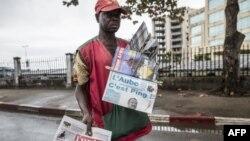Un marchand de journaux cherche des clients à un lampadaire à Libreville le 29 août 2016 tout en affichant des journaux locaux rapportant le résultat des élections présidentielles au Gabon.