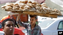 An Egyptian vendor carries bread downtown Cairo, Egypt, Aug. 5, 2013.