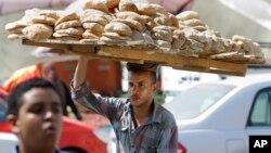 An Egyptian vendor carries bread downtown Cairo, Egypt, Aug. 5, 2013.