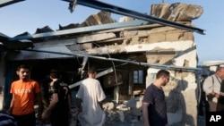 Người Palestine tụ tập bên ngoài một trường học LHQ ở trại tị nạn Jebaliya bị trúng đạn pháo kích của Israel, ngày 30/7/2014.