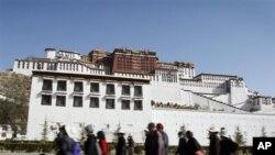 一群藏族民眾從拉薩布達拉宮前走過(資料照片)