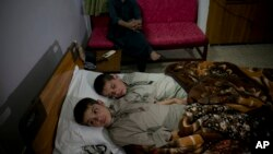 Abdul Rasheed, 9, front, and Shoaib Ahmed, 13, lie in a bed at a hospital in Islamabad, Pakistan, May 5, 2016. The boys are normal active children during the day, but lapse into a vegetative state — unable to move or talk - once the sun goes down.