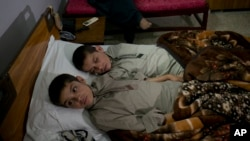 Abdul Rasheed, 9, front, and Shoaib Ahmed, 13, lie in a bed at a hospital in Islamabad, Pakistan, May 5, 2016. The boys, active during the day, lapse into a vegetative state after sunset. Dr. Javed Akram told AP he has no idea what is causing the symptoms.