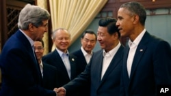 U.S. President Barack Obama, right, looks on China's President Xi Jinping, second right, shaking hands with U.S. Secretary of State John Kerry, left, at the start of a meeting after participating in the Asia Pacific Economic Cooperation (APEC) summit.