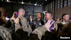 Soldiers take photos as U.S. President Barack Obama, center, shakes hands with troops after delivering remarks at Bagram air base in Kabul, Afghanistan, May 25, 2014.