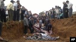 Tank ve top ateşinde ölenler, dün, Taftanaz kentinde toplu mezara gömülürken