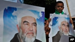 FILE - Palestinians in Gaza City carry pictures of Sheikh Raed Salah, leader of the Islamic Movement in Israel, during a protest to condemn what protesters claim was a desecration of Al-Aqsa Mosque in Jerusalem by Jewish extremists, Sept. 4, 2013.