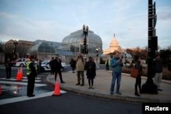 Personas en Washington, D.C., observan el paso de la carroza fúnebre con el cuerpo del expresidente George H.W. Bush, de camino al Capitolio para ceremonias fúnebres hasta el miércoles 5 de diciembre. Diciembre 3 de 2018.