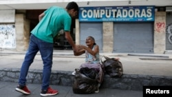 Mariano Marquez (L), a volunteer of Make The Difference (Haz La Diferencia) charity initiative, gives a cup of soup and an arepa to a homeless woman in a street of Caracas, March12, 2017.