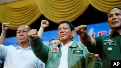 Presiden Filipina Rodrigo Duterte (tengah) berpose dengan tangan terkepal bersama Menteri Pertahanan Delfin Lorenzana (kiri) dan Panglima Militer Ricardo Visaya di kota Pasay, Filipina.(AP/Bullit Marquez)
