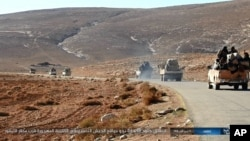 FILE - This image posted online on Saturday, Dec. 10, 2016, by supporters of the Islamic State militant group on an anonymous photo sharing website, purports to show a convoy of vehicles of IS driving in a desert area of east of Palmyra city, in Homs, Syr