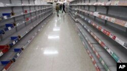 People shop for food from almost empty shelves at a big-box supermarket in Tokyo. Supermarket shelves are running empty despite authorities assuring citizens there is no need to panic from the crisis unfolding at a quake-stricken nuclear power plant, Marc