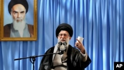 Iranian supreme leader's office, Supreme Leader Ayatollah Ali Khamenei delivers a speech in a ceremony marking the anniversary of the death of the late revolutionary founder Ayatollah Khomeini, shown in the picture at background, June 4, 2013.