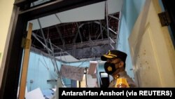Seorang petugas polisi berdiri di dekat ruang rusak di rumah sakit yang terkena gempa, Blitar, Jawa Timur, 10 April 2021. (Foto: Antara/Irfan Anshori via Reuters)