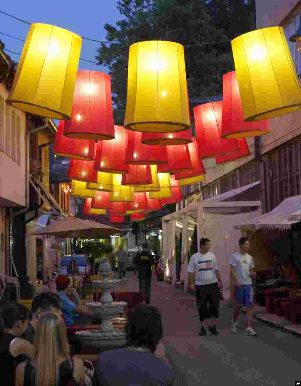 Na ulici u Sarajevu, ljudi prolaze kraj papirnatih svjetiljki koje se koriste kao ukrasi tokom ramazana
