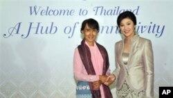 Aung San Suu Kyi (kiri) disambut oleh Perdana Menteri Thailand Yingluck Shinawatra dalam jamuan makan malam untuk seluruh peserta Forum Ekonomi Dunia di Bangkok, Thailand (31/5).