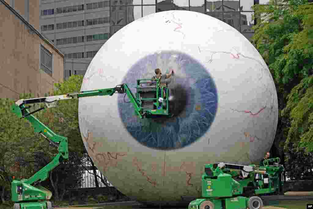 """Workers restore the fiberglass sculpture called """"The Eye"""" created by artist Tony Tasset in downtown Dallas, Texas. The he 30-foot giant eye was vandalized."""