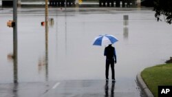 A man surveys floodwaters caused by heavy rains, May 25, 2013, in San Antonio.