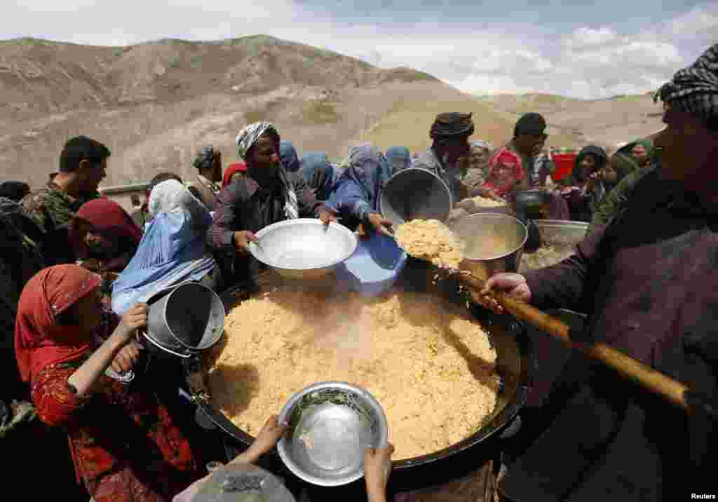 Villagers displaced by the recent deadly landslide receive their lunch in the Argo district of Badakhshan province, Afghanistan.