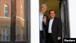 WikiLeaks founder Julian Assange waves from a window with Ecuador's Foreign Affairs Minister Ricardo Patino (R) at Ecuador's embassy in central London June 16, 2013.