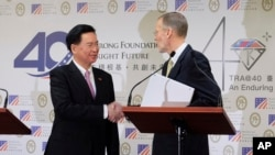 Taiwan Foreign Minister Joseph Wu, left, and American Institute in Taiwan (AIT) director William Brent Christensen shakes hands during a press conference in Taipei, Taiwan, March 19, 2019.