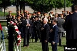 미국을 방문 중인 문재인 한국 대통령(오른쪽)이 30일 오전 마이크 펜스 부통령과 워싱턴 한국전 참전용사 기념비에 헌화한 후 양국 국기에 경례하고 있다.