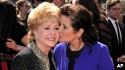 FILE - Debbie Reynolds (left) and Carrie Fisher arrive at the Primetime Creative Arts Emmy Awards in Los Angeles, Sept. 10, 2011.