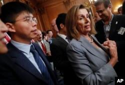 资料照片:美国众议院议长佩洛西(右)与香港活动人士黄之锋在美国首都华盛顿国会山举行香港人权问题记者会后对媒体讲话。(2019年9月18日)