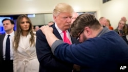 FILE - Pastor Joshua Nink, right, prays for Republican presidential candidate Donald Trump, after a Sunday service at First Christian Church, in Council Bluffs, Iowa.