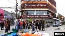 Para petugas tengah menginspeksi lokasi serangan bom di depan kedai kopi dan restoran Big Ben di propinsi Pattani (17/2). Dua orang relawan dilaporkan tewas dan 11 lainnya terluka dalam insiden ini.