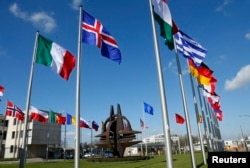 FILE - Flags fly at NATO headquarters in Brussels, Belgium, March 2, 2014. President Donald Trump has repeatedly asserted that member nations need to pay their fair share in defense spending.
