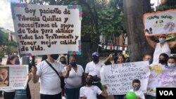 Pacientes con fibrosis quística y sus familiares sostienen su pancartas durante una protesta en Caracas, en octubre de 2021.