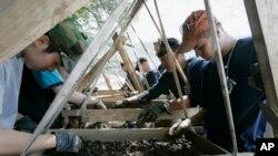 美国国防部战俘及战斗失踪人员联合司令部成员(右)与韩国军人一道寻找韩战美军遗骸。(2009年资料照)