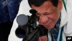 """Tổng thống Philippines Rodrigo Duterte kiễm tra súng trường tại căn cứ không quân Clark ở miền bắc Philippines. Ông Duterte tuyên bố sẽ """"ăn sống nuốt tươi"""" Abu Sayyaf vì đã chặt đầu thủy thủ Việt Nam."""