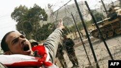 Người biểu tình phản đối la hét phía trước một xe tăng quân đội tại dinh tổng thống ở Cairo, ngày 11/2/2011