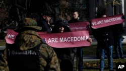 """A group of people hold banners reading """"We are Macedonia"""" during an anti-NATO protest in front of the Parliament in Skopje, Macedonia, while NATO Secretary General Jens Stoltenberg addresses the lawmakers in the Parliament building, Jan. 19, 2018."""