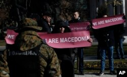 "FILE - A group of people hold banners reading ""We are Macedonia"" during an anti-NATO protest in front of the Parliament in Skopje, Macedonia, while NATO Secretary General Jens Stoltenberg addresses the lawmakers in the Parliament building, Jan. 19, 2018."