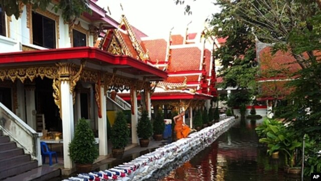 Thai monk watches flood Waters pushing Into Sai Mai Temple, which is north of Bangkok.