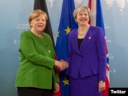 La canciller de Alemania, Angela Merkel (izq.) y la primera ministra de Gran Bretaña, Theresa May saludan antes de la reunión del G7 en Canadá. Junio 8 de 2018. Foto: @10DowningStreet.