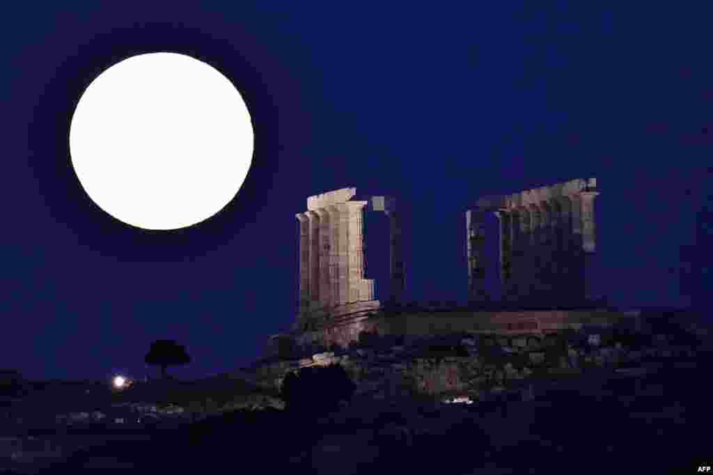Bulan purnama tampak di belakang kuil kuno Poseidon (Neptun) di Cape Sounion, tenggara Athena, Yunani.