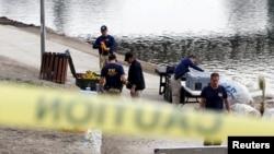 Agentes del FBI preparan equipo de buceo para buscar en el lago del parque Seccombe, en San Bernardino, California.