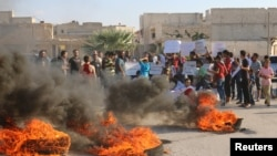 FILE - People gather near burning tires during a demonstration against forces loyal to Syria's president Bashar al-Assad and calling for aid to reach Aleppo near Castello road in Aleppo, Syria, Sept. 14, 2016.
